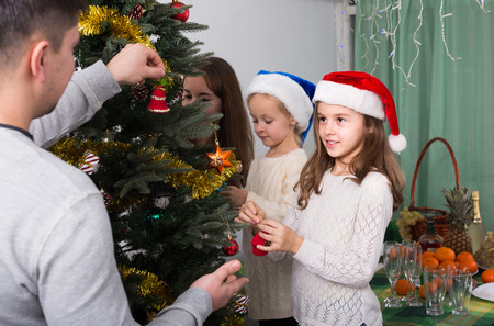 home decorating: Cheerful young parents and two little girls decorating Christmas tree together at home. Focus on girl Stock Photo
