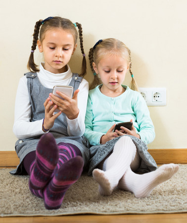 4s: Two little girls playing with smartphones at home