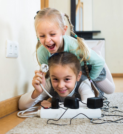 sockets: Careless children playing with sockets and electricity indoors