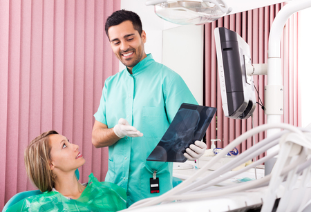 x ray equipment: happy male dentist and patient looking x-ray scan