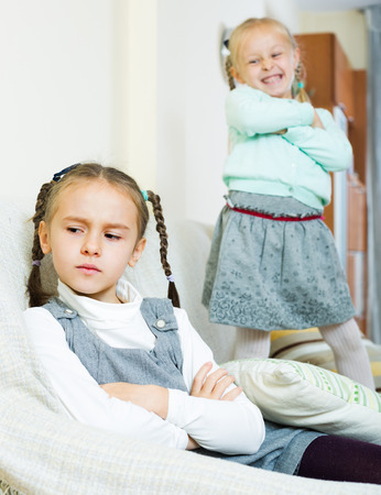 4s: Offended girl sitting apart of little sister after argue Stock Photo