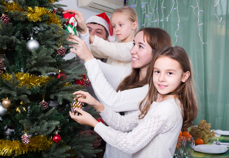 9 10 years: Happy family with two little daughters decorating Christmas tree together at home. Focus on girl