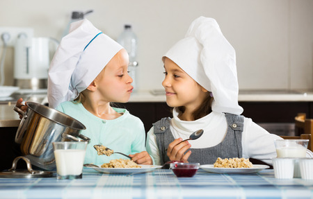 4s: Positive small girls eating healthy oatmeal at home kitchen