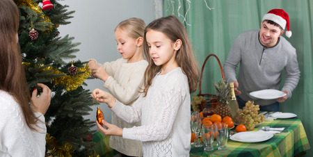 home decorating: Happy parents with children decorating Christmas tree with  love at home