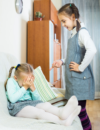 lecturing: american girl lecturing little sister in domestic interior. focus on blond girl
