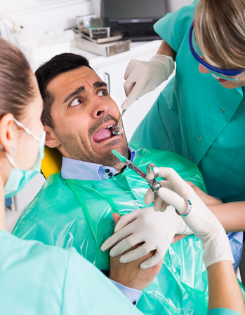 Portrait Of Doctor And Scared Patient At Dental Clinic Stock Photo