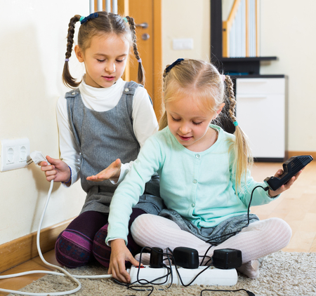 4s: Two little sisters with socket extender and charging units Stock Photo