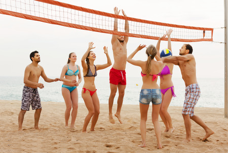 freetime activity: Happy friends playing volleyball at sandy beach Stock Photo