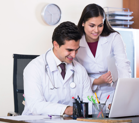 physiotherapists: Two smiling professional doctors brainstorming and sharing information in clinic