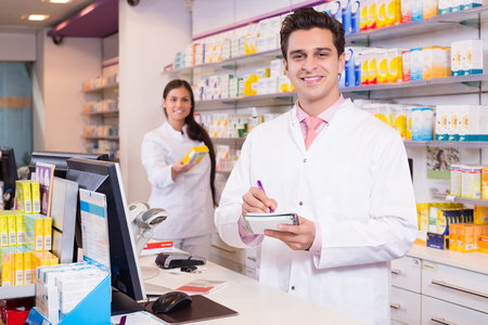 farmacy: Portrait of happy pharmacist and assistant working at farmacy reception Stock Photo