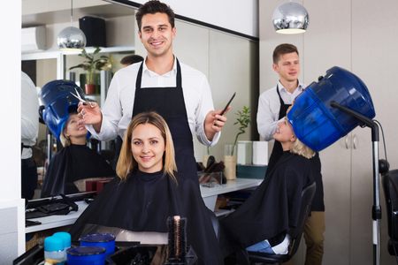 hairdressing saloon: Cheerful  young man cutting long hair of girl in hairdressing saloon