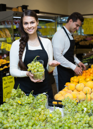 25s: Portrait of two happy russian workers with seasonal fruits, prices on Spanish