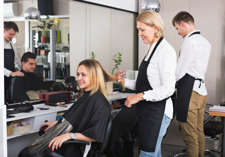 19's: Positive aged woman cutting girl hair in hairdressing saloon