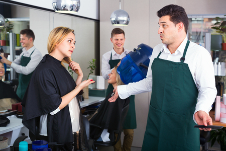 haircutter: Young upset woman blaming hairdresser in bad haircut Stock Photo