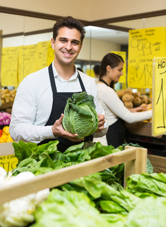 25 30: Smiling seller in apron in vegetables market with cabbage, prices on Spanish