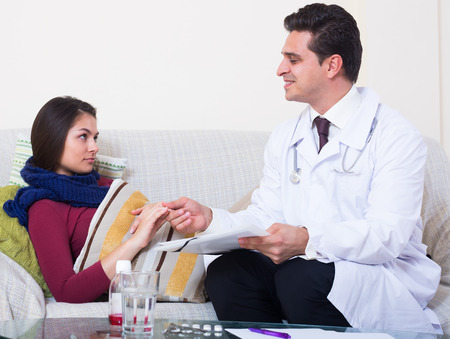 complaining: Young woman with cold and fever complaining to therapeutist
