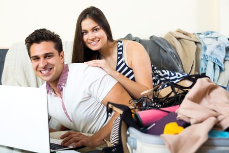 spouses: Smiling young spouses browsing web and packing luggage at home