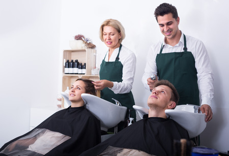 19's: Two hairdressers working with hair of clients in washing tray. Selective focus on guy