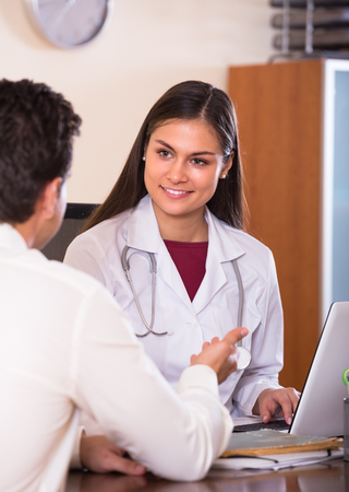 therapeutist: Portrait of patient and smiling young female therapeutist at desk in modern clinic