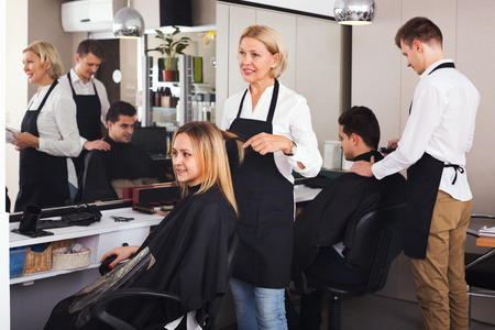 19's: Smiling aged woman cutting girl hair in the barbershop Stock Photo