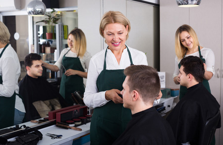 16s: Mature hairdresser cutting hair of teenager in salon