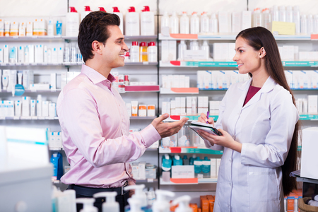 pharmacist: Helpful pharmacist serving and consulting man in pharmacy