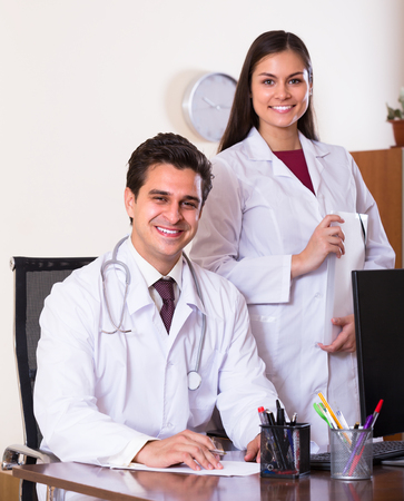 physiotherapists: Two smiling doctors therapeutists with stethoscope posing in private clinic