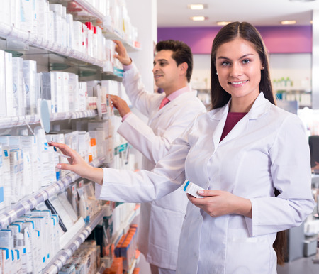 people working: Smiling pharmacist and pharmacy technician posing in drugstore with healthcare