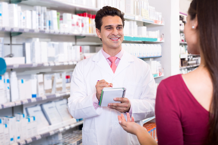 dispensary: Smiling experienced pharmacist counseling female customer