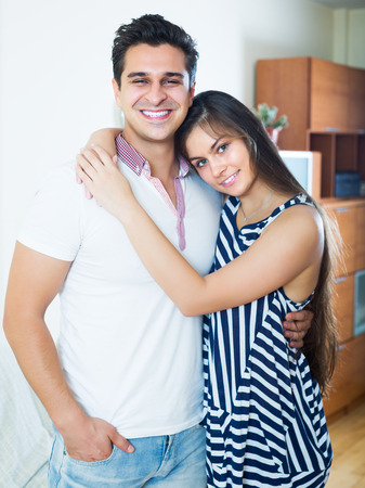 limp: Portrait of positive girlfriend and boyfriend cuddling at home Stock Photo