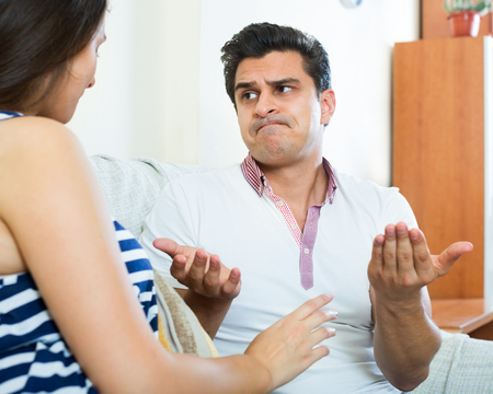 spouses: Angry young spouses having domestic argue in a living room at the home