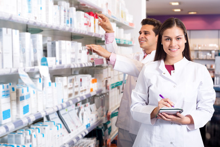 adult indian: Portrait of two friendly pharmacists working in luxury pharmacy Stock Photo