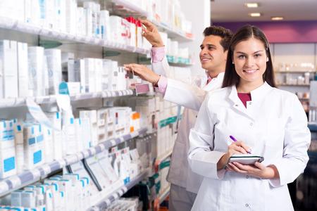 Retrato de dos farmacéuticos cómodos que trabajan en farmacia de lujo