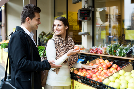 spouses: Young positive spouses choosing sweet fruits in grocery outdoors Stock Photo