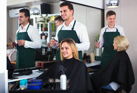 peignoir: Cheerful young man cutting long hair of girl in hairdressing saloon