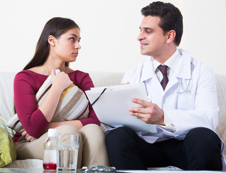 25 35: Professional doctor paying female patient a visit for checkup