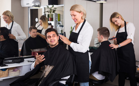 16s: Elderly female hairdresser cutting hair of Indian guy in barbershop