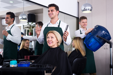 18's: Professional stylist cutting hair of elderly blonde in salon. Focus on the woman