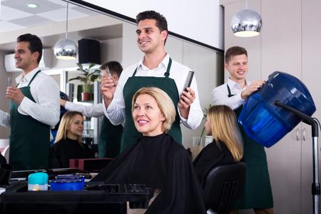 hair stylist: Professional stylist cutting hair of elderly blonde in salon. Focus on the woman