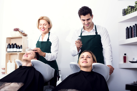 19's: Two hairdressers working with hair of clients in washing tray. Focus on girl