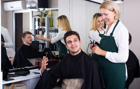 16s: Mature female doing hairstyle for adult man in hairdressing saloon Stock Photo