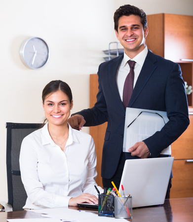 co operation: Successful businessman and his smiling young  assistant at the desk in modern office Stock Photo