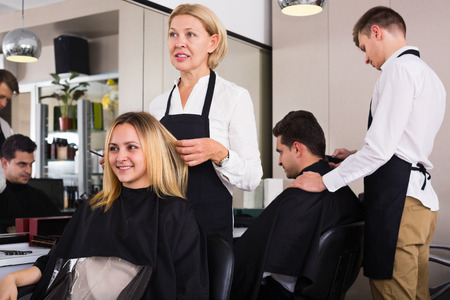 19's: Cheerful aged woman cutting girl hair in the barbershop Stock Photo