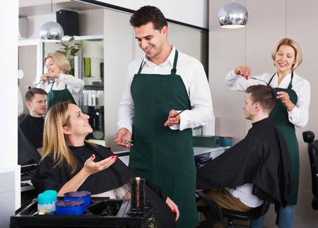 18's: Cheerful young man cutting long hair of beautiful girl in hairdressing saloon Stock Photo