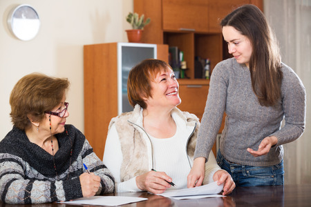 75s: Female agent consulting positive elderly women in office