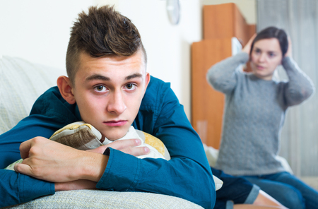 criticize: Upset mother and frustrated teenage son arguing in domestic interior
