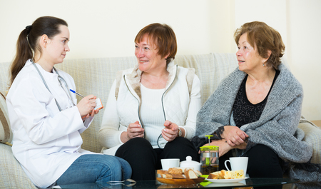 therapeutist: Two senior women discussing health problems with female therapeutist