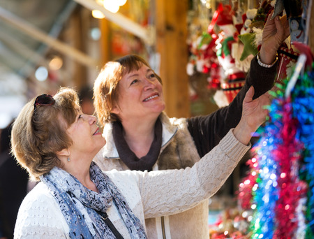 70 75 years: Cheerful mature women walking on the Christmas market and choosing jewelry Stock Photo