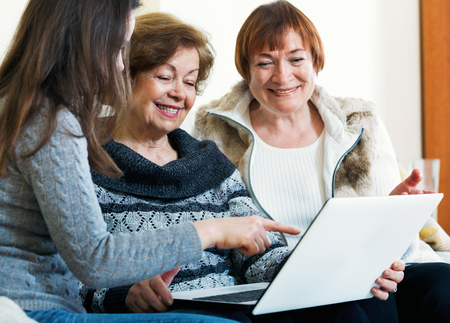 relative: Smiling female pensioners and young cute relative browsing web on laptop