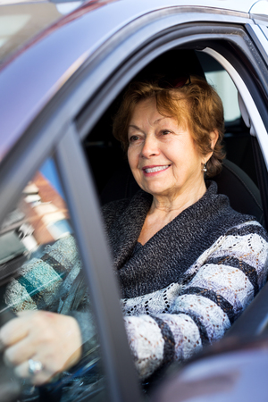 75s: Attractive mature woman sitting in new car at driver seat